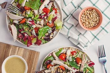 Bols de salades mélangées avec tomates, pignons, huile d'olive