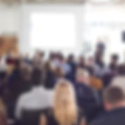 Backs of many people sitting in a conference or meeting venue looking at a speaker who stands next to a presentation, leading the meeting or conference, as many corporate events in which DMC Sicily and DMC Puglia worked as a meeting planner, or conference planner.