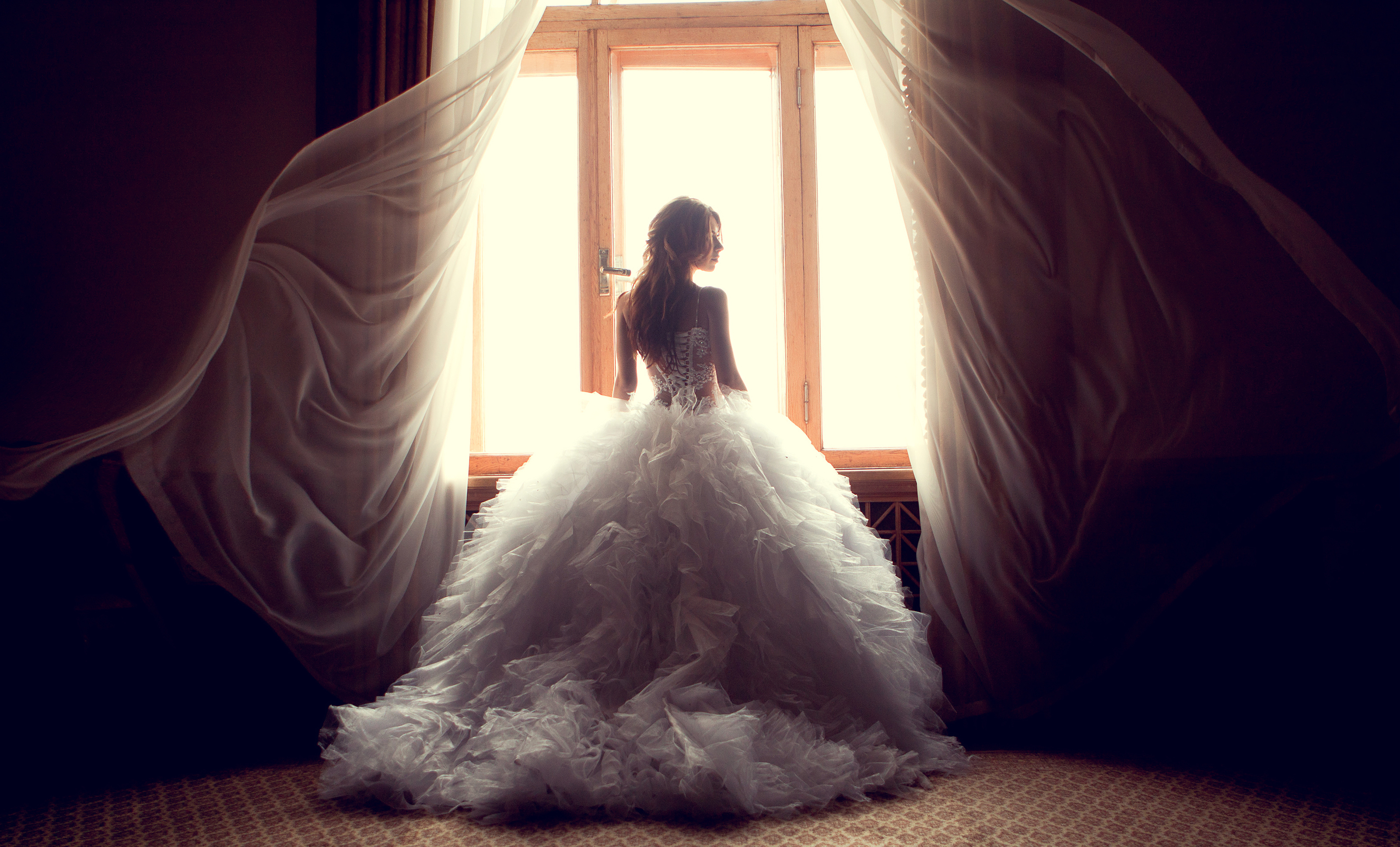 Portrait of the beautiful bride against a window indoors