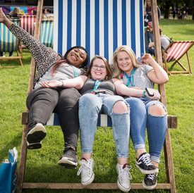 Corporate event photography of girls having fun in a big chair
