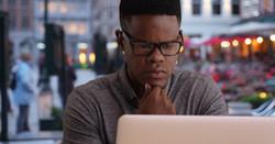 Black man working on computer shuttersto