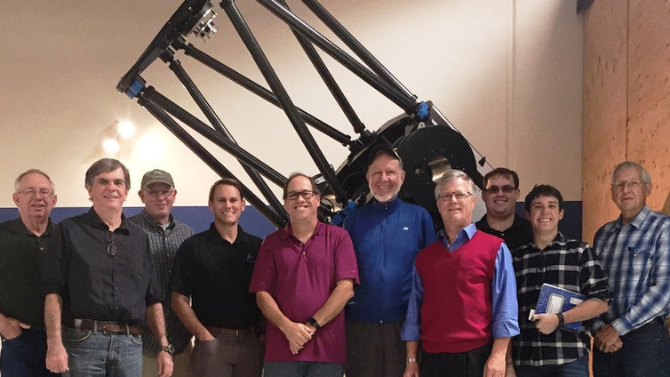The 1-meter telescope, shown in the factory with engineers and supporters, is the third in a line of direct-drive telescopes.  First was the Cal Poly 18-inch aperture telescope built by students at California Polytechnic State University, San Luis Obispo. Second was the 0.7-meter PlaneWave Instruments CDK-700 telescope of which 50 are conducting research every night at observatories around the world.