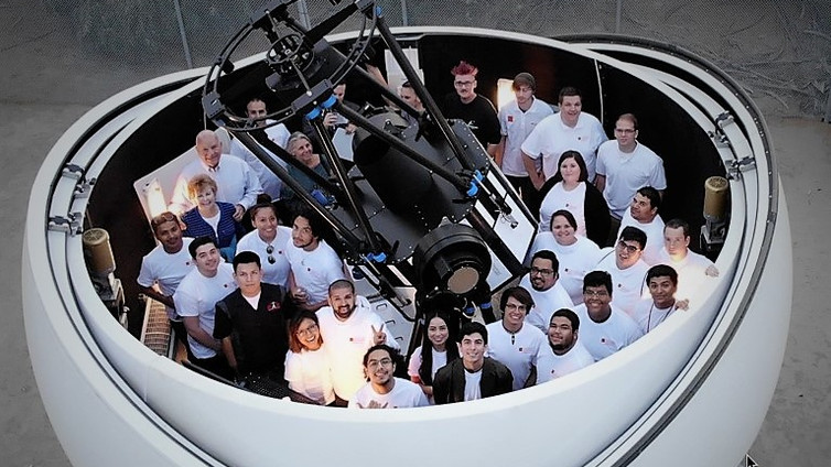 Astronomy Research Seminar student teams and astronomy club members gather around the PlaneWave Instruments 1.0 meter fully robotic telescope at the College of the Desert's Mary Reagan Observatory. Located at 138 feet below sea level, this is the lowest research observatory in the world.