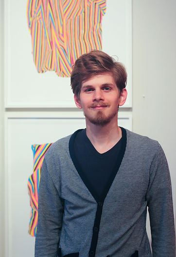 A portrait of the artist, Justin Rubich, in front of his Stripescape lithographs.