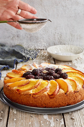 Peach Cake with Blackberries and sugar sifting