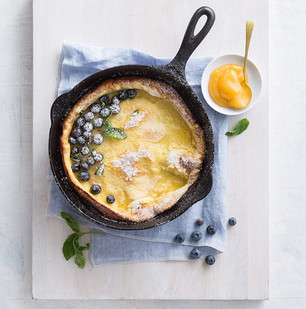 Dutch Baby in Cast Iron Skillet with Blueberries and Peach Curd