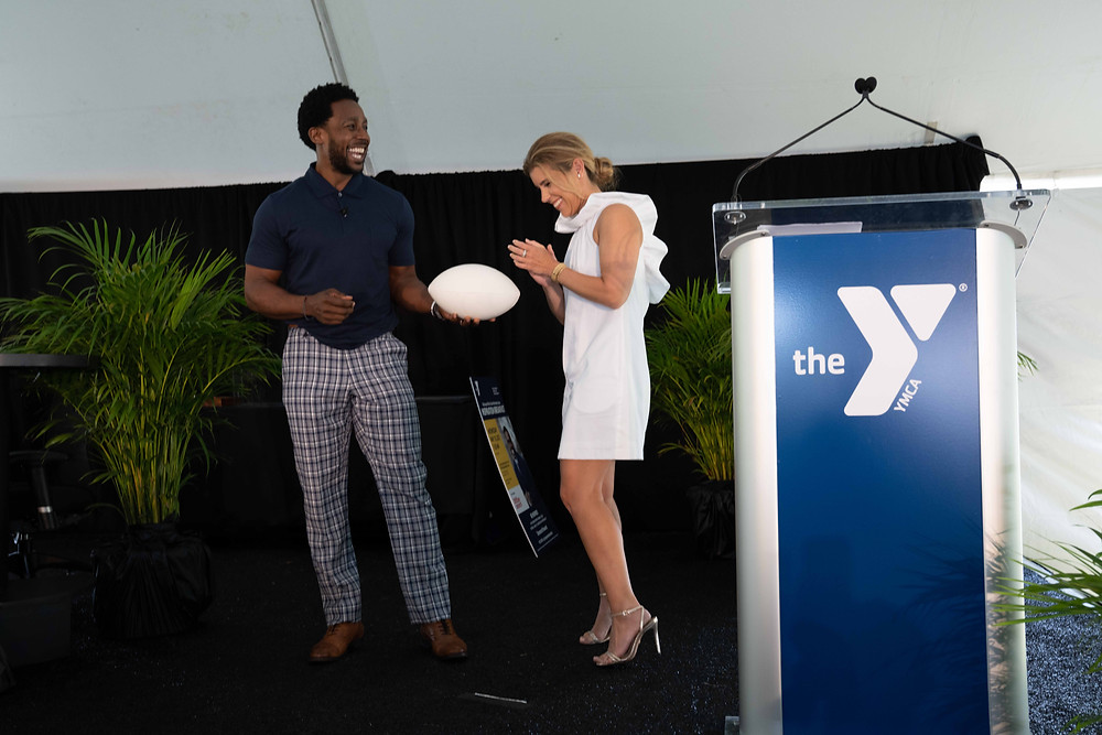 ESPN's Desmond Howard hands the ball off to journalist and emcee Paige Kornblue to teach her his famous Heisman pose