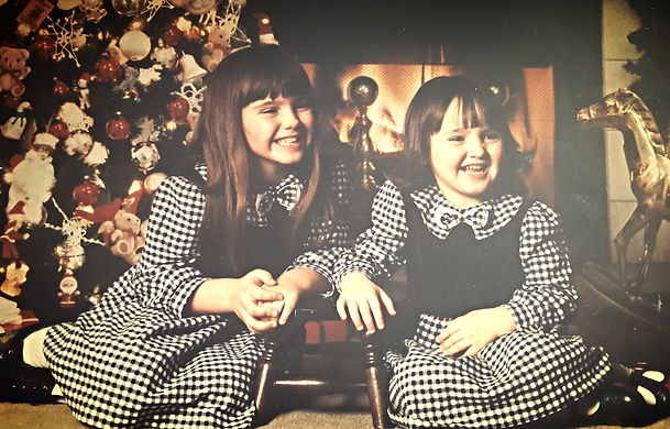 my sister and I in matching dresses posed in front of a fire