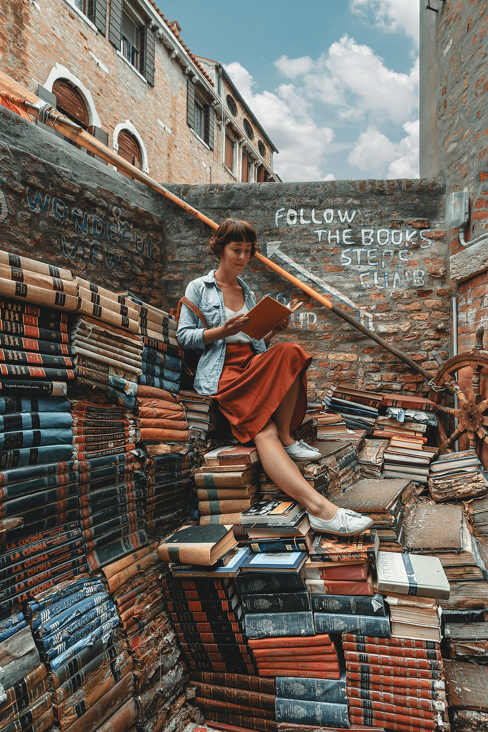 Young woman reading on a pile a books