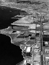 The new Montgomery Freeway began the transition to the Interstate 5 highway system that opened access to the dredged-in Tidelands shown in this Rozelle aerial of 1956 as light-colored land south of the Navy's mothball fleet.