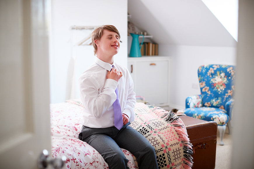 Young Downs Syndrome Man Sitting On Bed