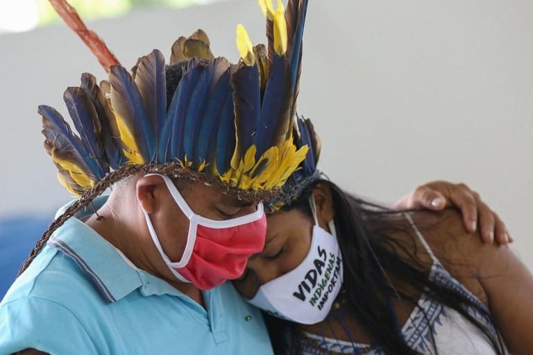 Fotografia de um homem e uma mulher indígenas. Ambos estão com foco na parte do peito para cima. O homem usa uma camiseta polo azul, um cocar de penas azuis e amarelas e máscara branca e vermelha. Ele está com a mão esquerda no ombro da mulher. A mulher está com uma blusa de alcinha branca com detalhes em azul, seus cabelos são longos e pretos e estão soltos. Ela utiliza uma máscara branca com o escrito: vidas indígenas importam. Sua cabeça está recostada no peito do homem.