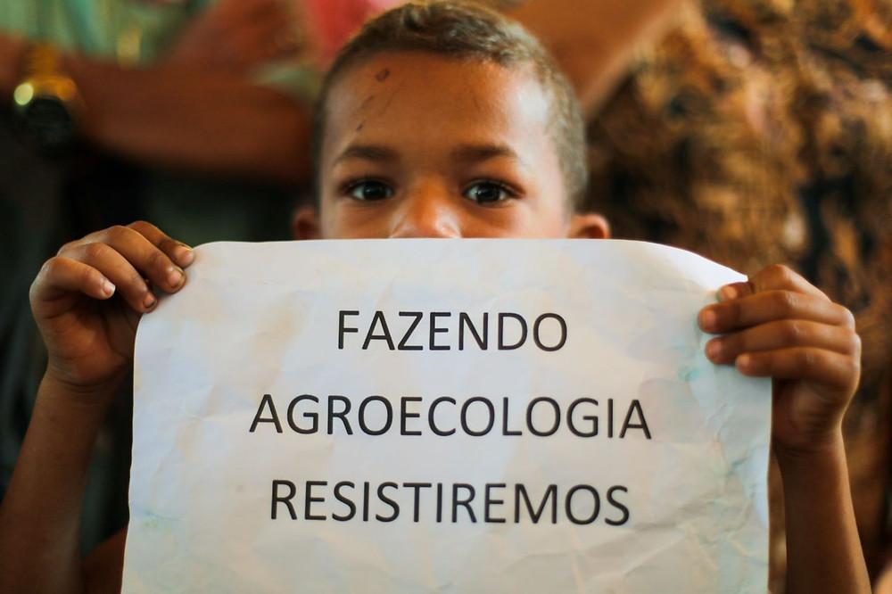 Fotografia de um garoto negro que segura uma folha de papel abaixo do nariz com a frase: Fazendo agroecologia resistiremos.