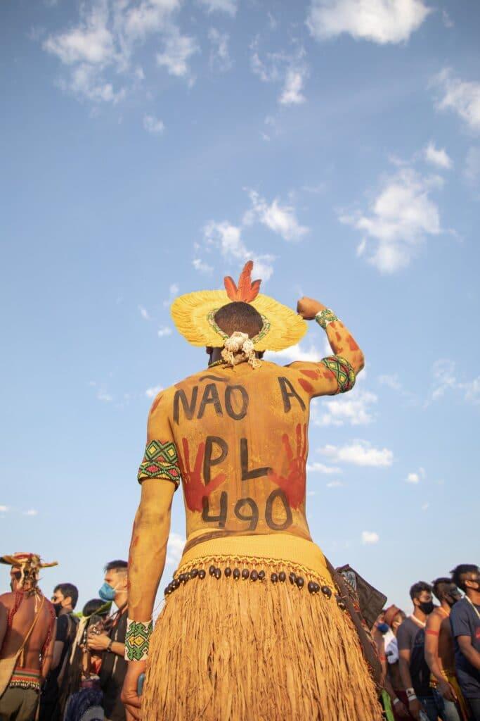 Fotografia de um homem indígena de costas. A fotografia mostra o homem das coxas para cima em um ângulo de baixo para cima. O homem está utilizando uma saia de palha com um cinto feito de contas, assim como pulseiras e braceletes coloridos em ambos os braços, além de um cocar amarelo com penas vermelhas. Em suas costas com tinta lê-se a frase: não a PL 490. O homem está com o braço direito levantado para cima com o punho fechado. A frente dele estão outros indígenas e acima dele é possível ver o céu azul e com algumas nuvens.