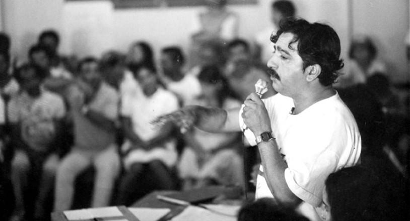 Fotografia em preto e branco que mostra em primeiro plano Chico Mendes, um homem branco de cabelos e bigodes pretos, da cintura para cima, vestindo uma camiseta branca e segurando um microfone enquanto está com o braço direito levantado gesticulando. Em segundo plano há pessoas asssistindo seu discurso.