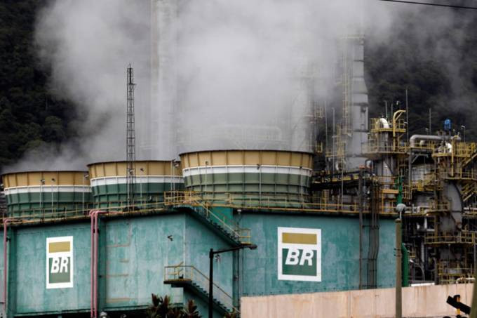 Fotografia que mostra diversos tonéis da Petrobrás emitindo muita fumaça. Os tonéis possuem as cores verde, branco e amarelo e estão envoltos por uma espécie de muro azul