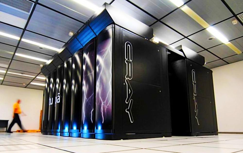 Fotografia de um supercomputador preto com estampas de raio e luzes azuis nas partes de cima e baixo. O supercomputador lembra uma cpu gigante e vai do chão até o teto, ao fundo uma pessoa borrada passa e nos dá a dimensão do equipamento, maior que um adulto de estatura média.
