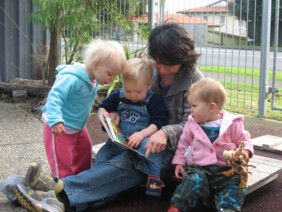A teacher reads a story outside.