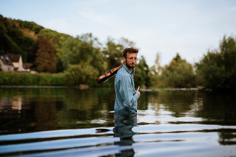 Tong music Violinist and Singer-Songwriter Tonio Geugelin standing fully clothed in a lake with his violin and looking into the camera