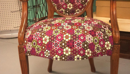Chaise antique recouverte d'un coton aux motifs géométriques.