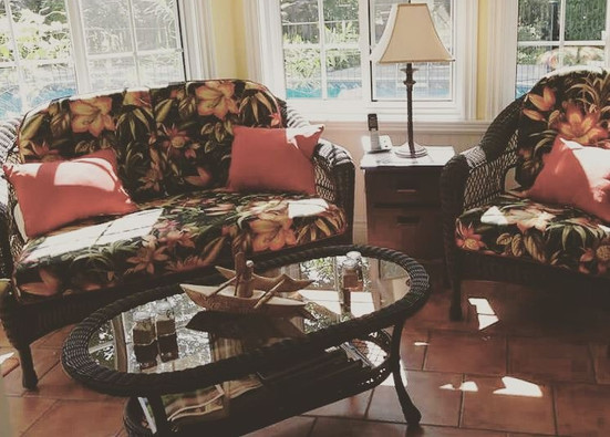 Causeuse et fauteuil en rotin munies de coussins motif floral.