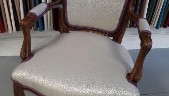 Chaise antique recouverte d'un tissu argenté.