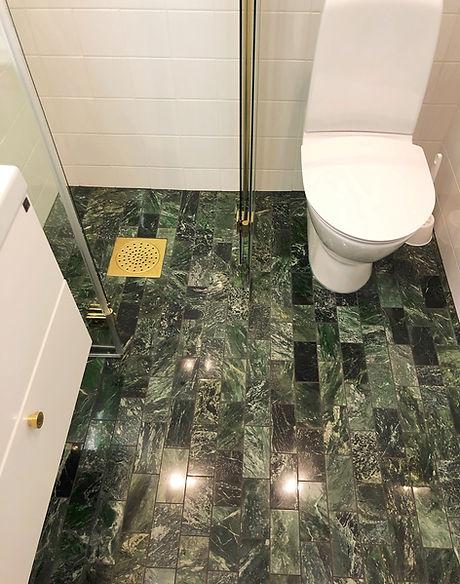 Badrum i Nacka med grön marmor och mässing, badrummet renoverades av Badrumsgruppen