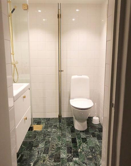 Badrum med grön marmor och mässing, badrummet renoverades av Badrumsgruppen