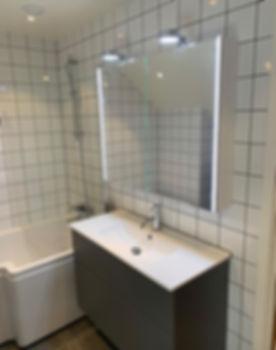 Badrumskommod, spegelskåp och badkar i badrum efter renovering