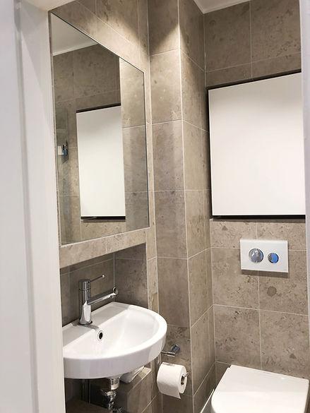 Litet badrum med Bricmate granitkeramik på golv och vägg