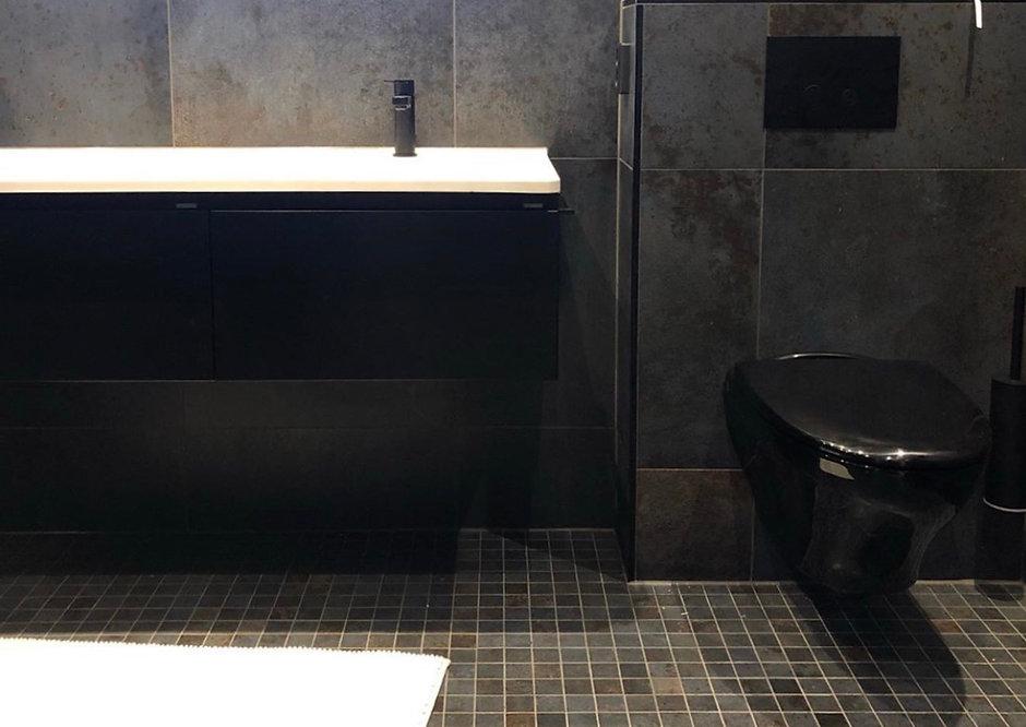 Badrum med metallic klinker, svarta detaljer och svart kommod, renoverat av Badrumsgruppen i Göteborg