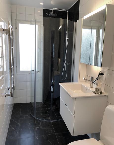 Badrum i Järfälla med svart marmor, duschvägg, kommod och toalett