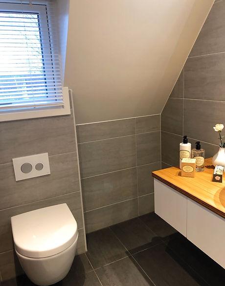 Vägghängd toalett med fixtur och spolknapp från Tece och kommod från INR