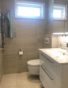 Kommod, vägghängd toalett med spolknapp från Tece och handdukstork i badrum på Ekerö renoverat av Badrumsgruppen