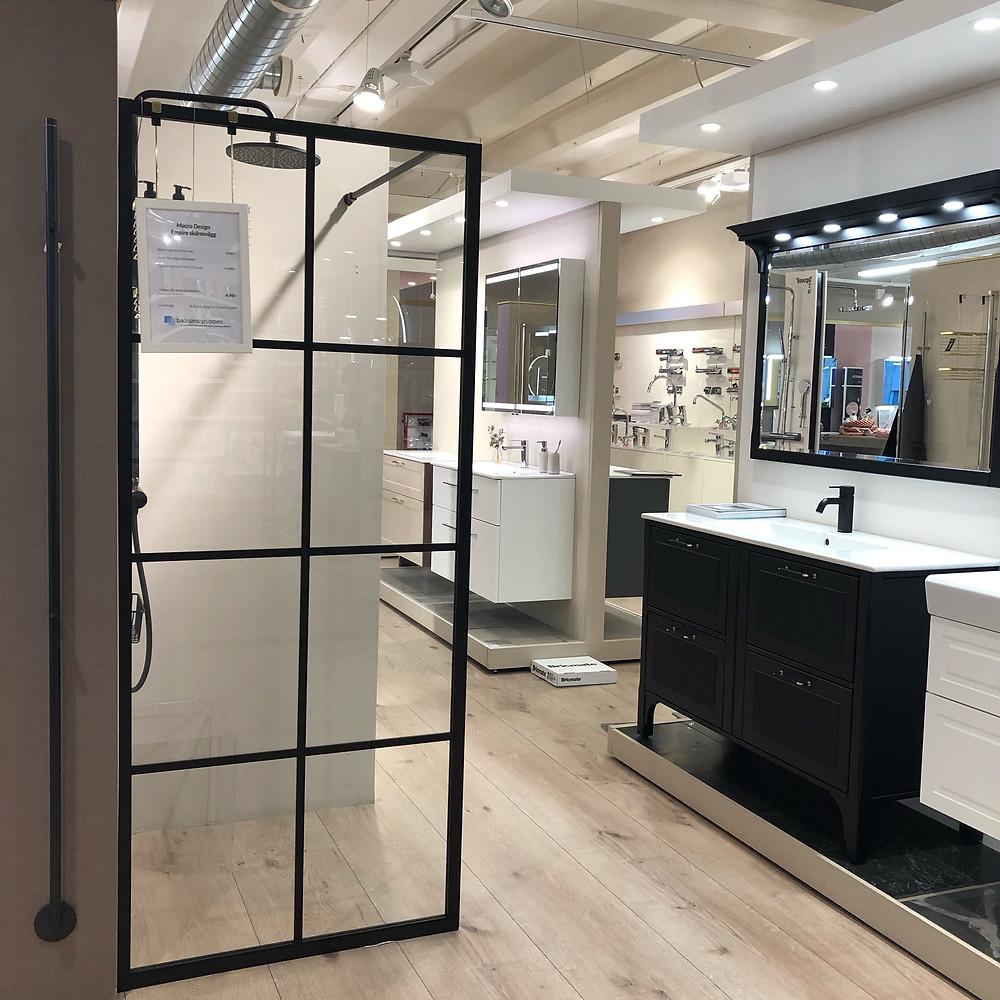 Badrumsutställning i Badrumsgruppens butik i Bromma, i utställningen finns duschvägg med spröjs och svart handdukstork samt svart takdusch