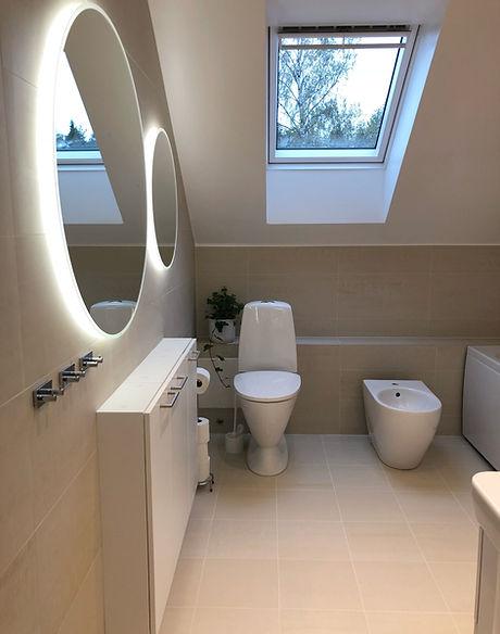 Badrum med takfönster efter renovering, badrummet har speglar, toalett och badrumsförvaring