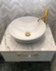 Tvättställ i porslin med blandare i mässing och bänkskiva i marmor