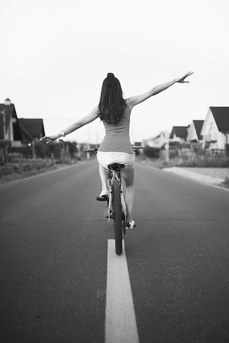 Girl riding a bike in the city. Back vie