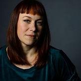 Profilbild av Erica Elfström. Kvinna med rött hår och lugg tittar in i kamrean. Bilden har mörk bakgrund.