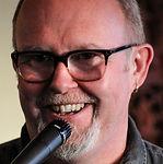 Profilbild av Colm Ò Ciarnàin. En man med skägg och glasögon ler mot publiken. Framför honom står en mikrofon.