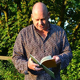 A profile picture of Dominic Williams. A man with a shirt is reading a book in front of a tree.