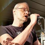 Profilbild av Frank Bergsten, en man med glasögon håller en mikrofon och talar till en publik.