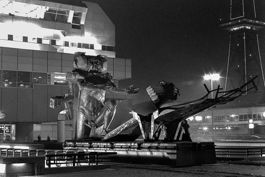 'Ecbatane - man builds his city' statue at night