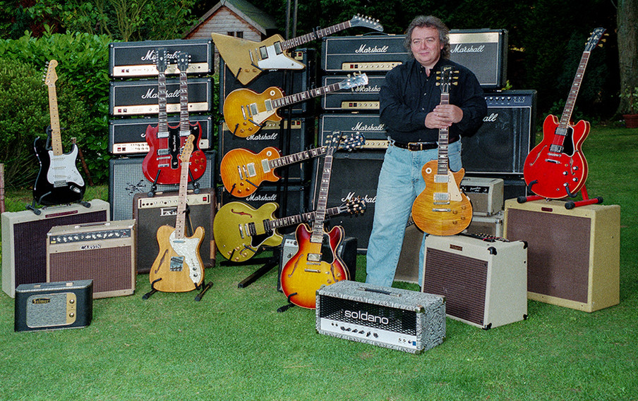 Bernie holding 'The Beast' in front of Marshall & Other Amps & Guitars