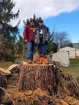 owner scott drake and son scottie standing on large tree stump