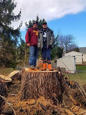 Owner Scott Drake and son Scottie standing on massive tree stump in NY