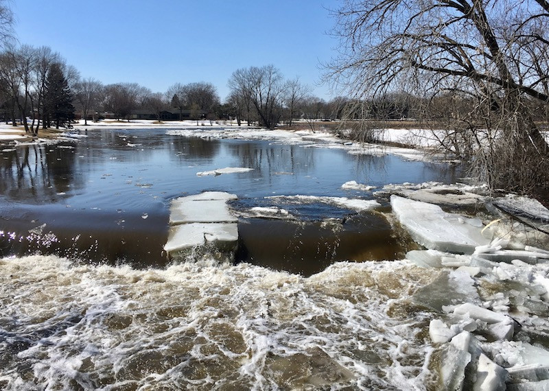 Early spring nature scene of ice floating down a creek and ober a dam