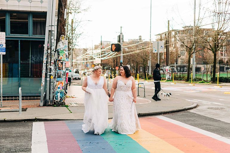 Two brides in white wedding dresses hold hands and cross a rainbow crosswalk in Capitol Hill, Seattle on their elopement day