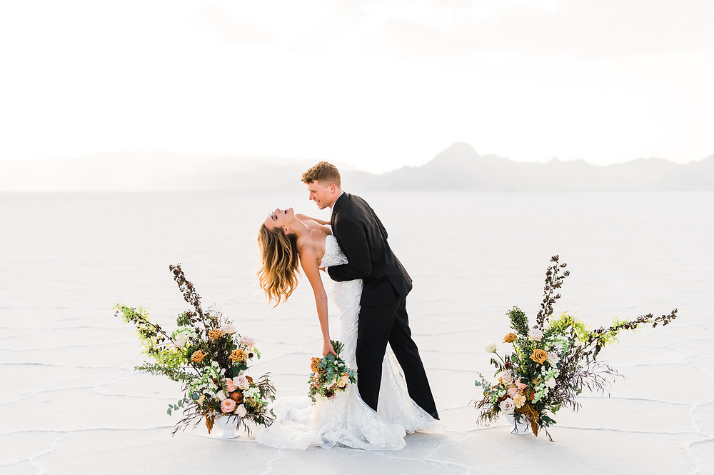 A couple in wedding attire stands between two floral vases on the flat white landscape of the bonneville salt flats