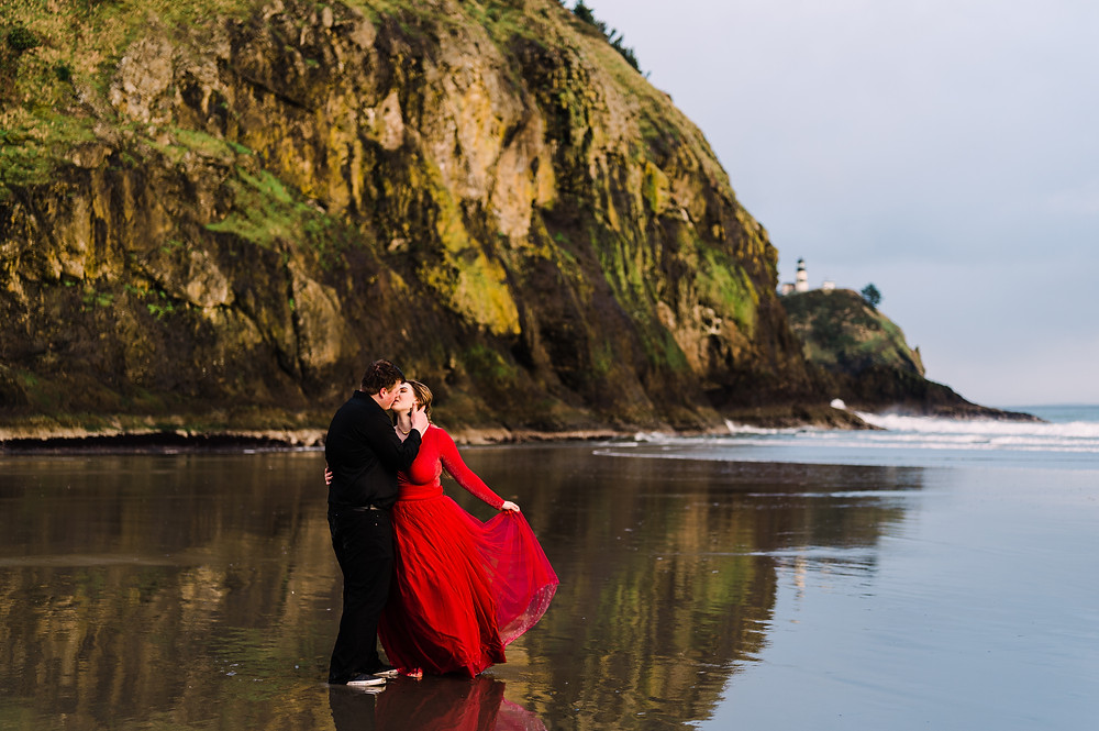 A woman holds the skirt of her dress out of the water while embracing her partner on a beach on the Washington coast